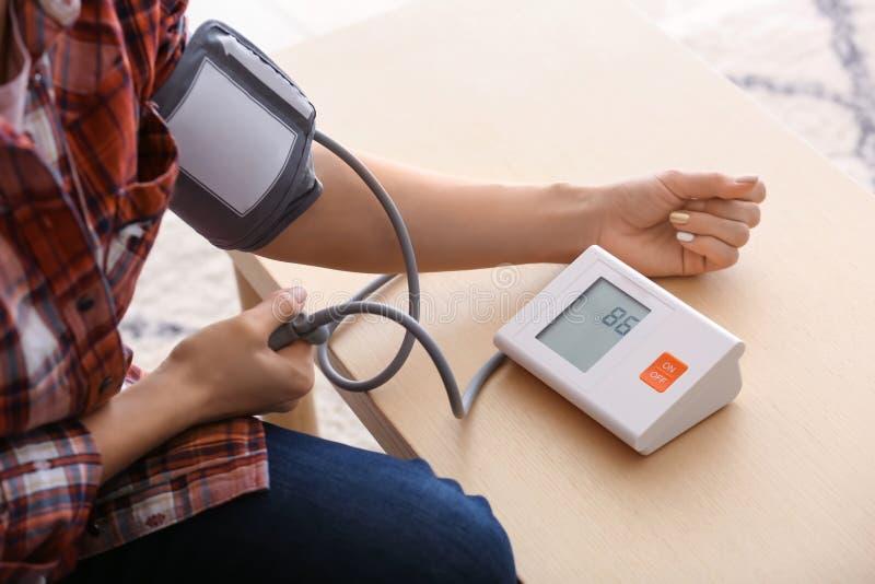 Jovem mulher que mede sua pressão sanguínea em casa fotos de stock
