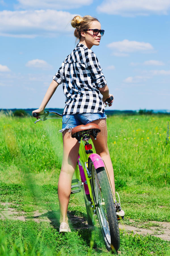 Jovem mulher que monta sua bicicleta fora imagens de stock