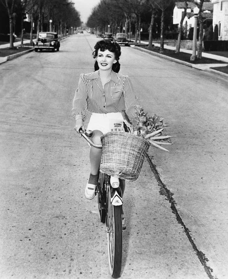 Jovem mulher que montam sua bicicleta com a cesta completa das flores e cenouras (todas as pessoas descritas não são umas vivas m foto de stock royalty free