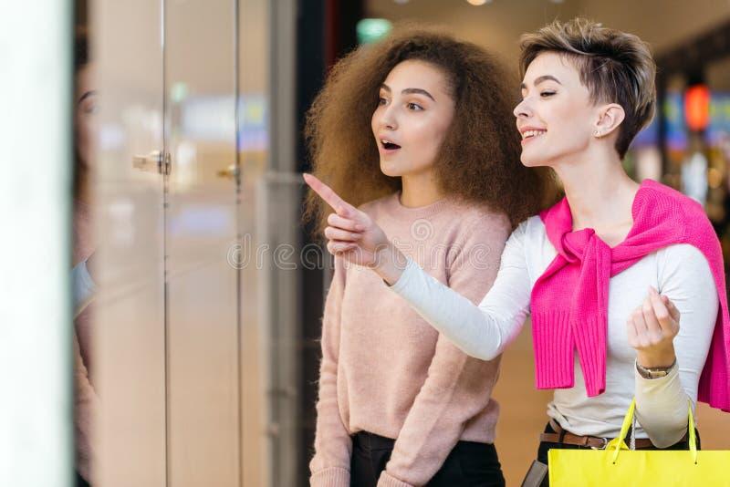 Jovem mulher que mostra algo na janela da loja a seu marido imagem de stock
