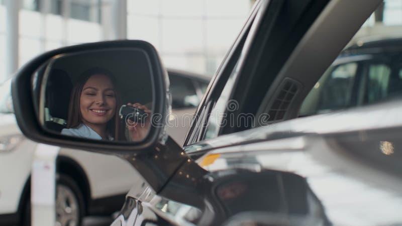 Jovem mulher que mostra a chave ao carro novo fotografia de stock