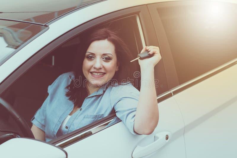 Jovem mulher que mostra chaves novas do carro, efeito da luz foto de stock