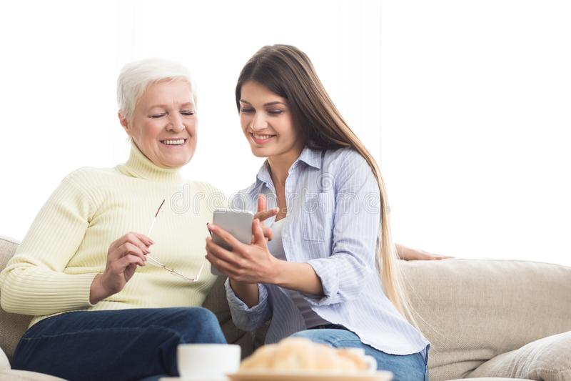 Jovem mulher que mostra fotos para serir de mãe, usando o smartphone fotografia de stock