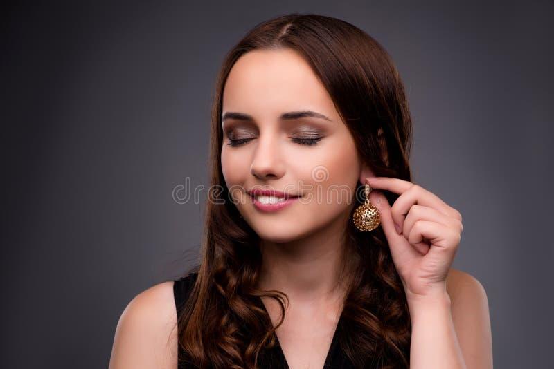 A jovem mulher que mostra lhe brincos novos fotografia de stock