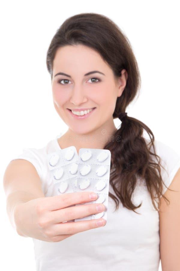 Jovem mulher que mostra o pacote dos comprimidos isolados no branco imagem de stock