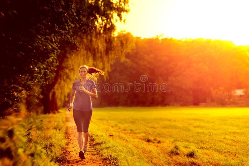 Jovem mulher que movimenta-se ao longo de uma trilha do país fotografia de stock royalty free