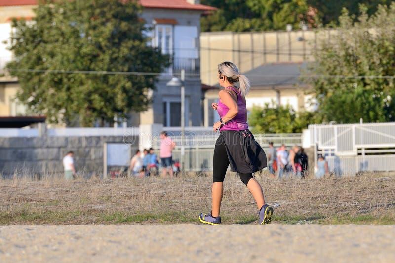 Jovem mulher que movimenta-se na areia fotos de stock royalty free