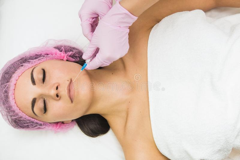 Jovem mulher que obtém a injeção cosmética na clínica da beleza fotos de stock