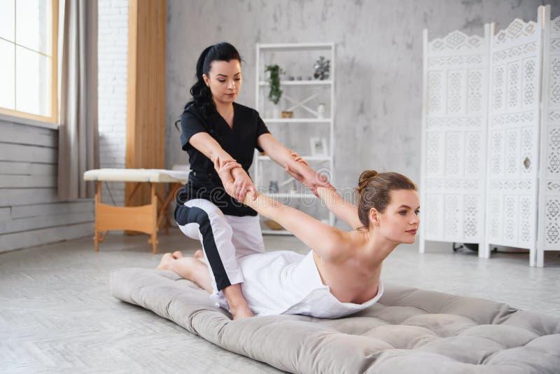 Jovem mulher que obtém a massagem de esticão tailandesa tradicional pelo terapeuta isolado no fundo branco fotos de stock