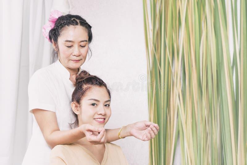 Jovem mulher que obtém a massagem do ombro e do pescoço em termas tailandeses foto de stock royalty free