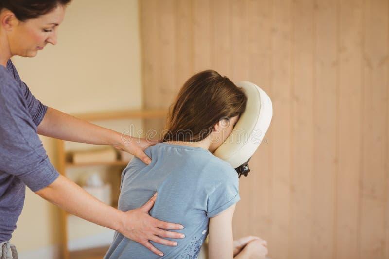 Jovem mulher que obtém a massagem na cadeira foto de stock royalty free