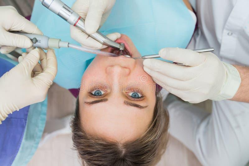 A jovem mulher que obtém o close up dental do tratamento, as mãos do dentista e o assistente faz procedimentos do tratamento à fê imagens de stock
