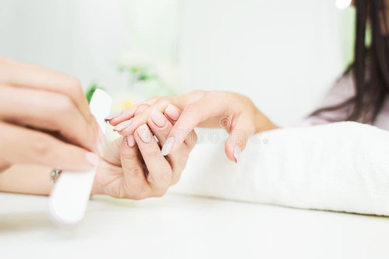 Jovem mulher que obtém o tratamento de mãos no salão de beleza imagens de stock