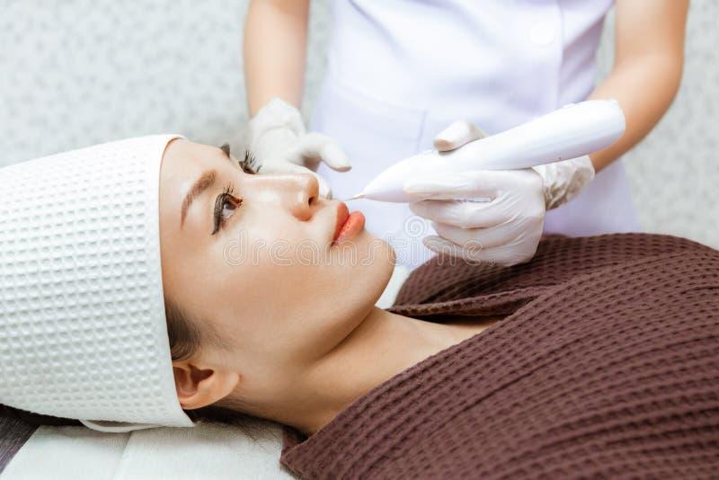 Jovem mulher que obtém seu tratamento da beleza por um doutor em uma clínica da beleza foto de stock