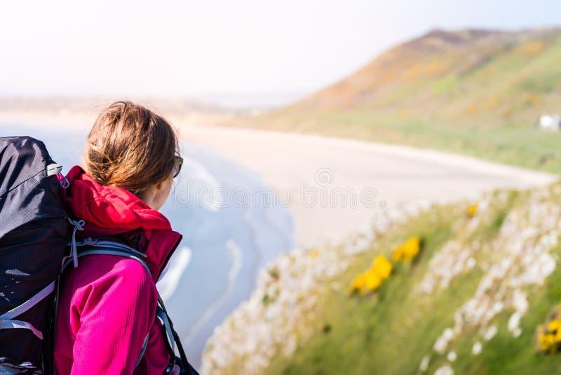Jovem mulher que olha à distância de Cliff Over The Seashore me imagem de stock royalty free