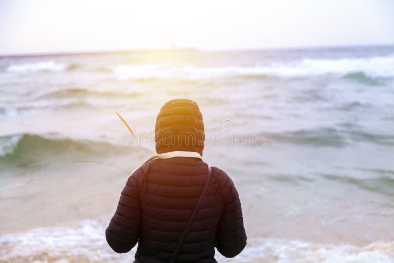 Jovem mulher que olha apenas o nascer do sol foto de stock royalty free