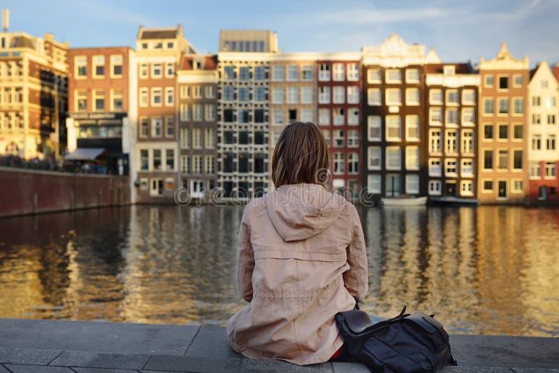 Jovem mulher que olha as casas de dança famosas de Amsterdão no dia ensolarado imagens de stock royalty free