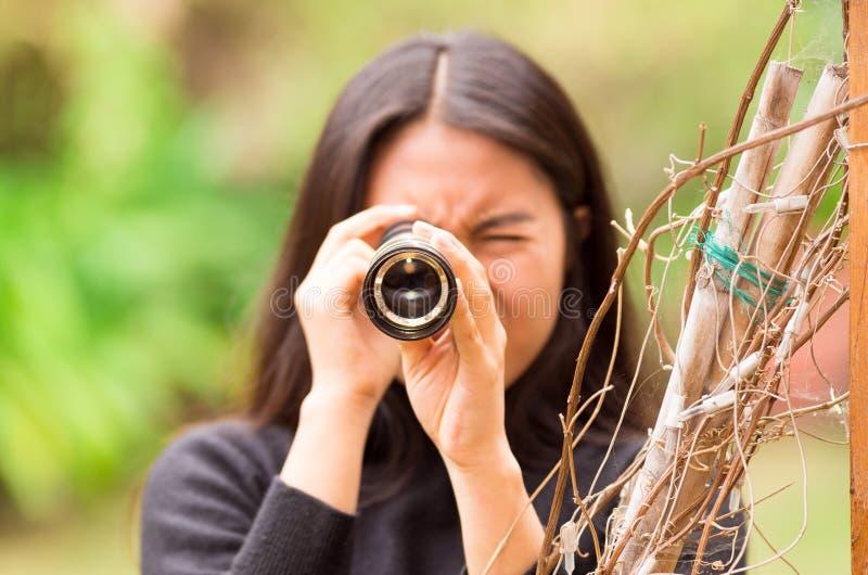 Jovem mulher que olha através do monocular preto na floresta em um fundo borrado foto de stock royalty free