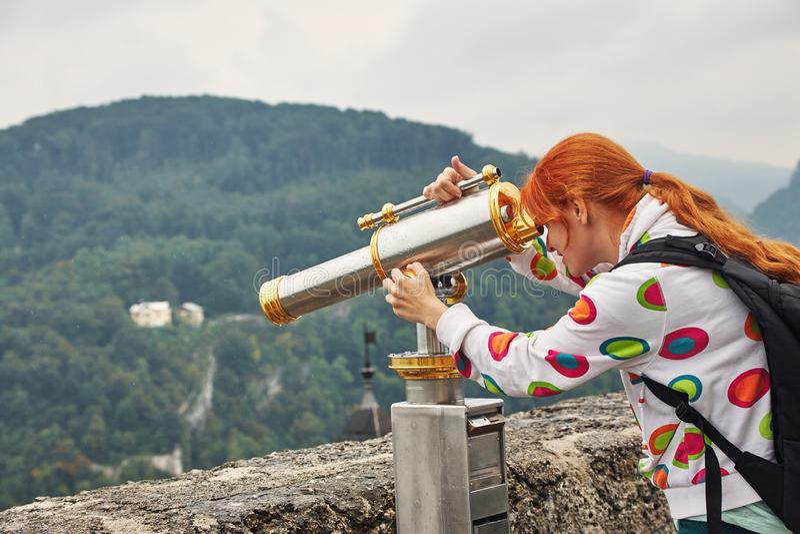 Jovem mulher que olha através do telescópio sightseeing uma cidade com uma plataforma de observação fotografia de stock royalty free