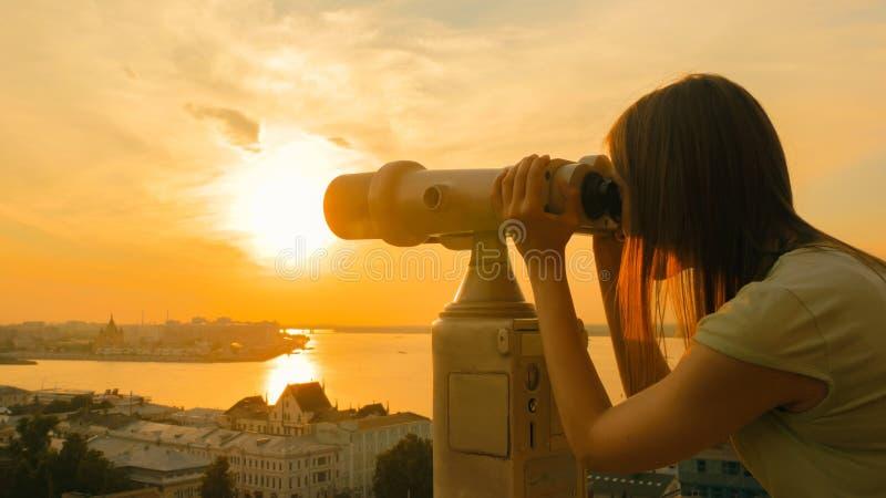 Jovem mulher que olha atrav?s do telesc?pio do turista, parte hist?rica de explora??o da cidade foto de stock royalty free