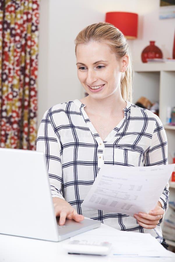 Jovem mulher que olha contas domésticas imagem de stock royalty free