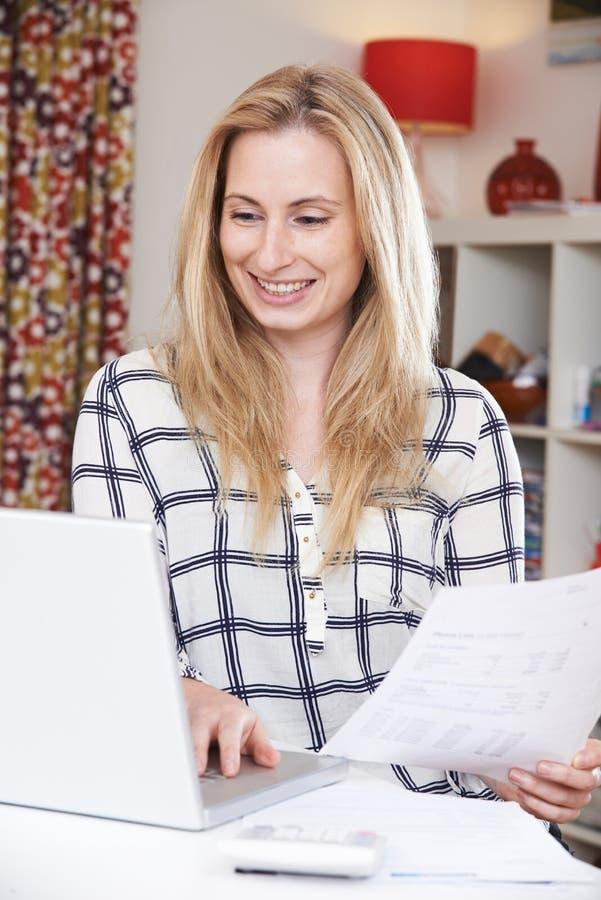 Jovem mulher que olha contas domésticas imagens de stock royalty free