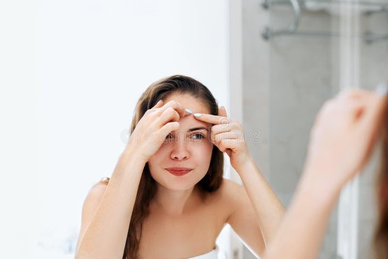 Jovem mulher que olha e para espremer a acne em uma cara na frente do espelho Menina feia da pele do problema, menina adolescente fotos de stock
