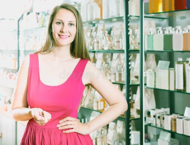 Jovem mulher que olha entusiasmado e que compra no supermarke do perfume imagem de stock
