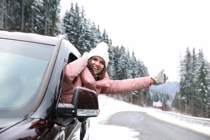 Jovem mulher que olha fora da janela de carro na estrada imagens de stock