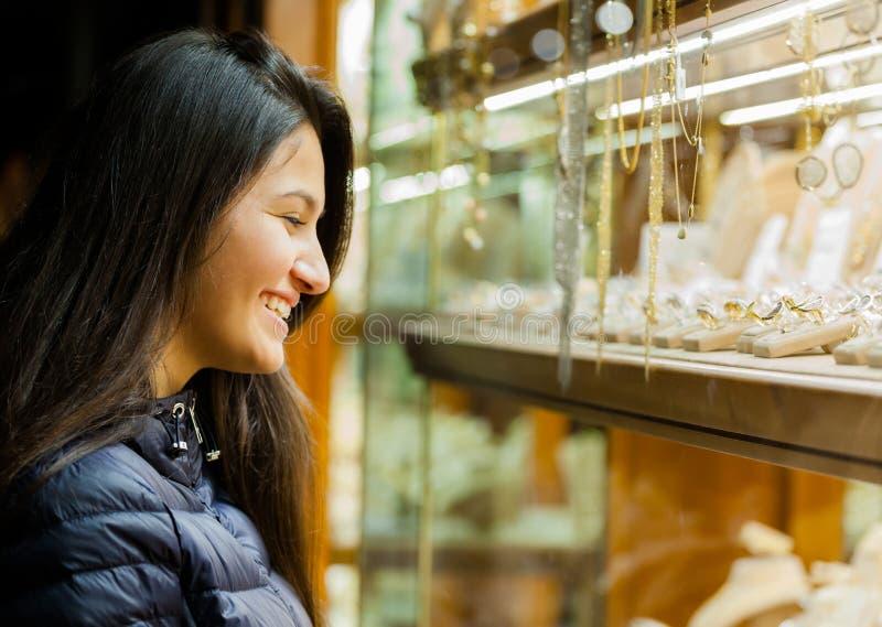 Jovem mulher que olha a mostra de uma joia exterior imagem de stock