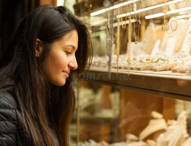 Jovem mulher que olha a mostra de uma joia exterior fotografia de stock