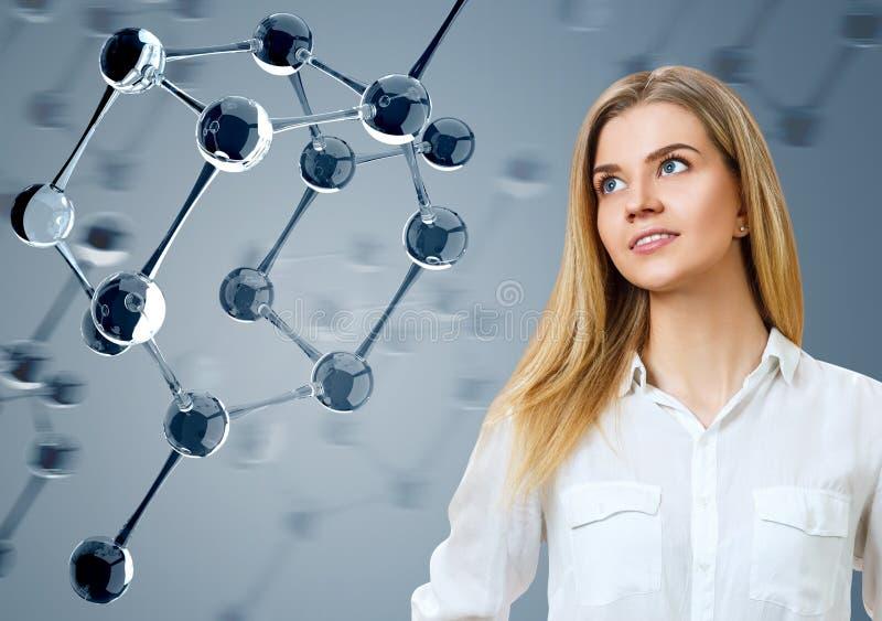 Jovem mulher que olha nas moléculas de vidro foto de stock royalty free