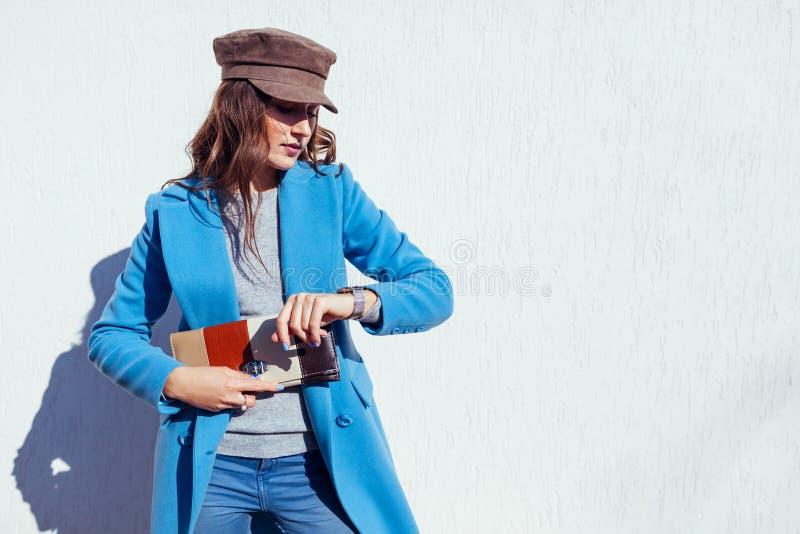 Jovem mulher que olha no relógio, guardando a bolsa e vestindo o revestimento azul Roupa e acessórios fêmeas da mola Forma fotos de stock