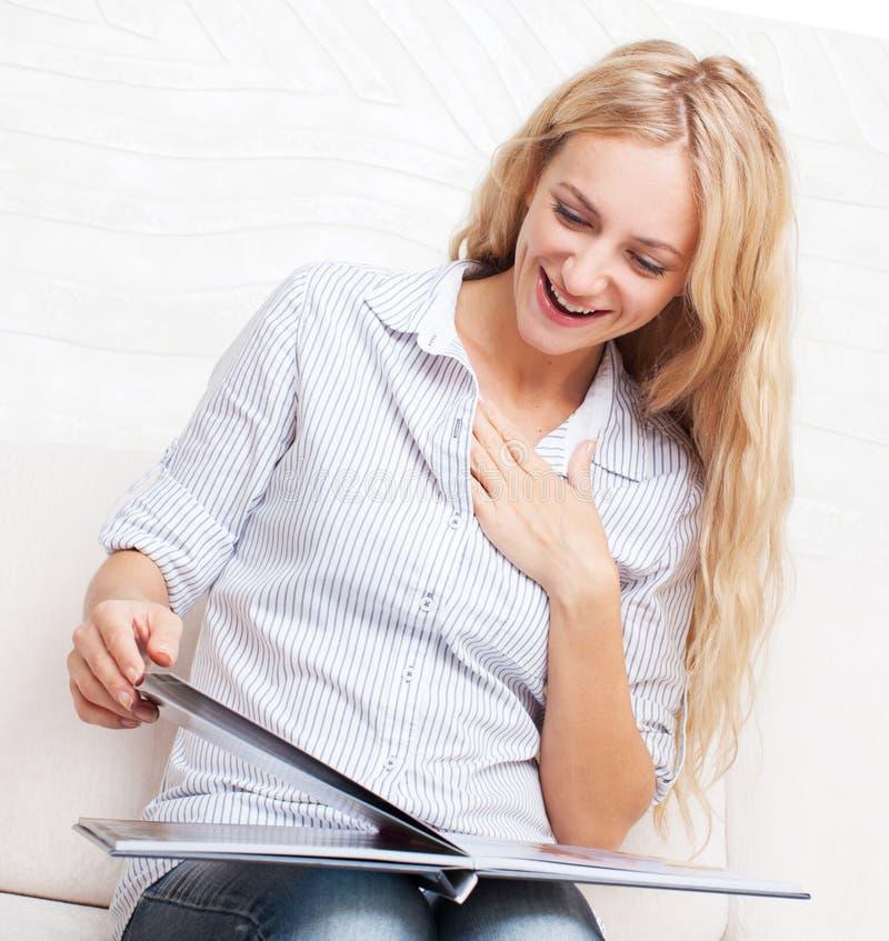 Jovem mulher que olha o livro da foto fotos de stock royalty free