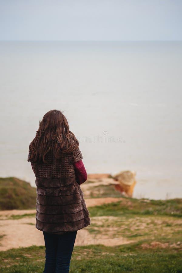 Jovem mulher que olha o mar que está apenas na costa fora foto de stock royalty free