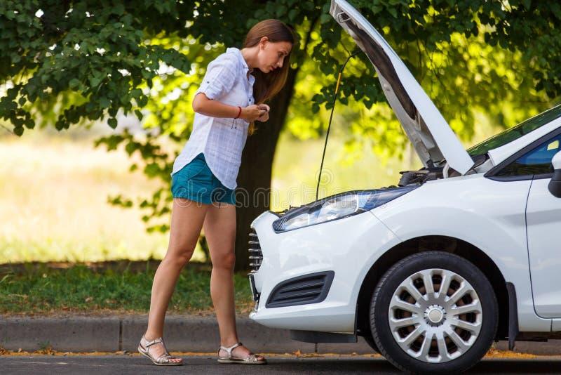 Jovem mulher que olha o motor de carro quebrado fotografia de stock