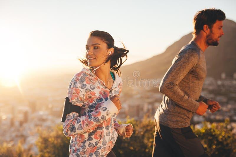 Jovem mulher que olha para trás ao correr foto de stock