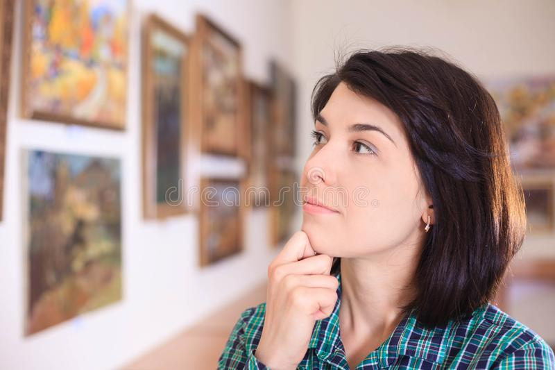 Jovem mulher que olha a pintura fotos de stock