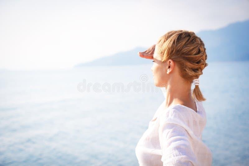 Jovem mulher que olha sobre o horizonte imagens de stock