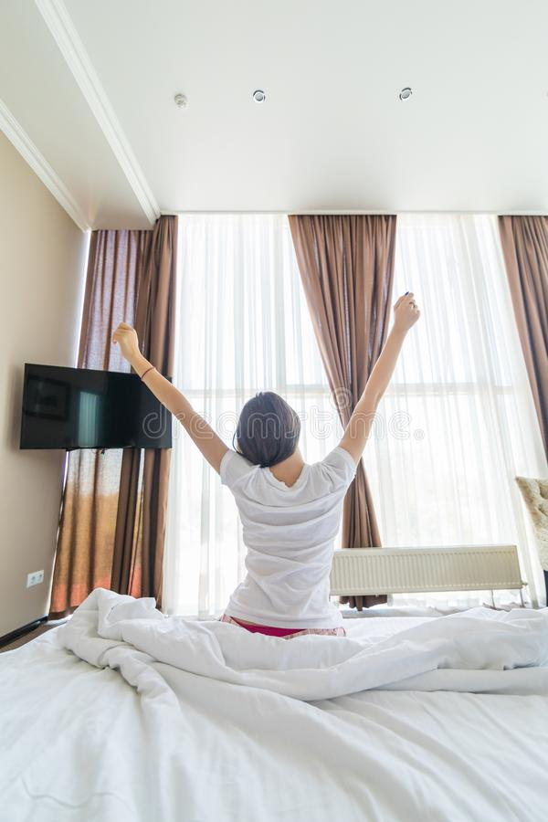 Jovem mulher que outstretching seus bra?os que sentam-se na cama ap?s a boa noite de sono, pouco disposta levantar-se e deixar se fotos de stock