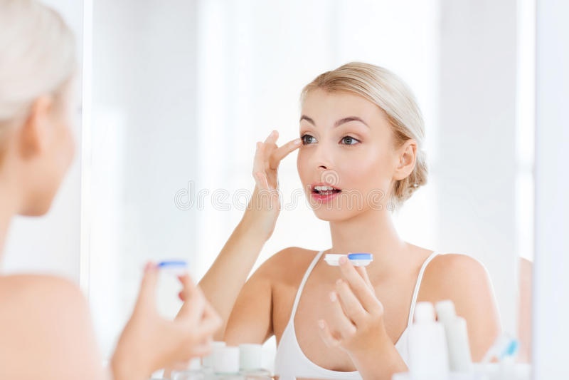 Jovem mulher que põe sobre lentes de contato no banheiro fotos de stock