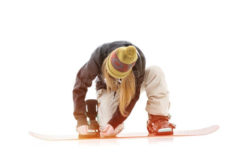 Jovem mulher que põe sobre o snowboard fotografia de stock