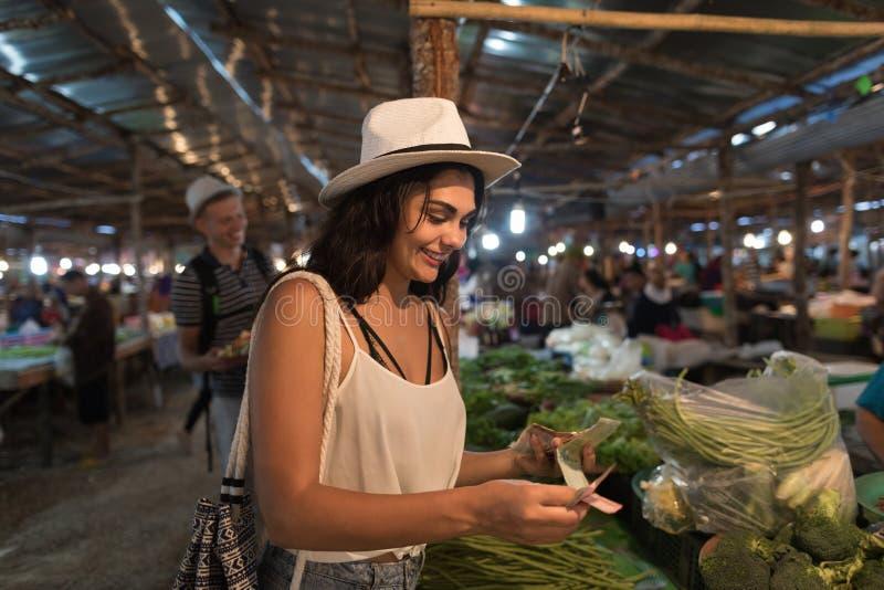 Jovem mulher que paga o dinheiro por legumes frescos na compra da menina do mercado no bazar da rua fotos de stock