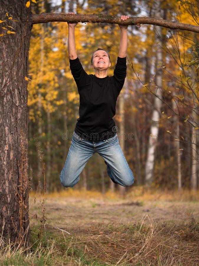 Jovem mulher que pendura em um ramo com uma expressão esticada em sua cara foto de stock royalty free