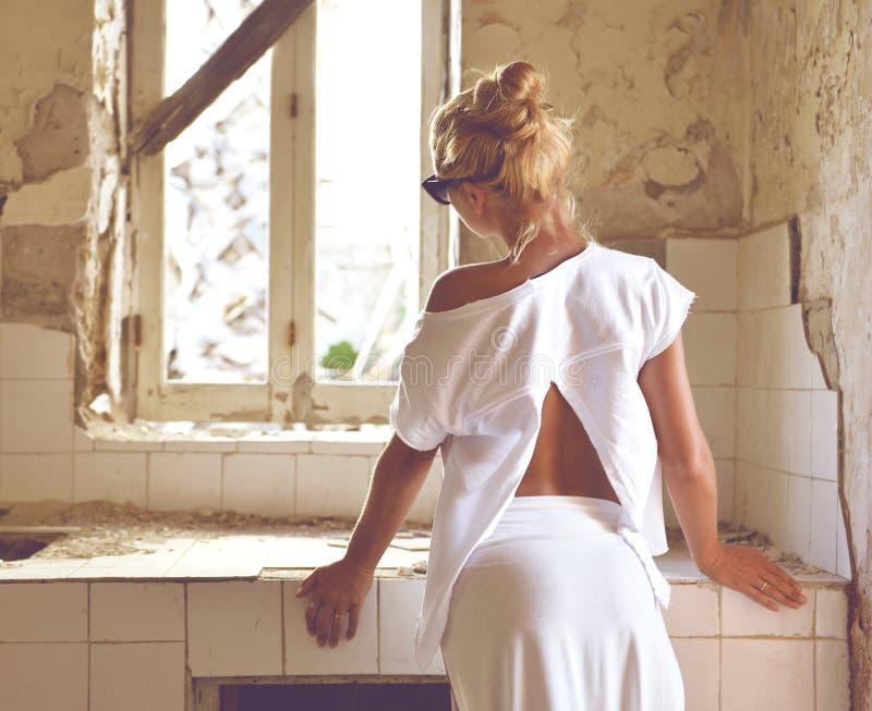 Jovem mulher que pensa de remodelar a cozinha velha da casa imagens de stock royalty free