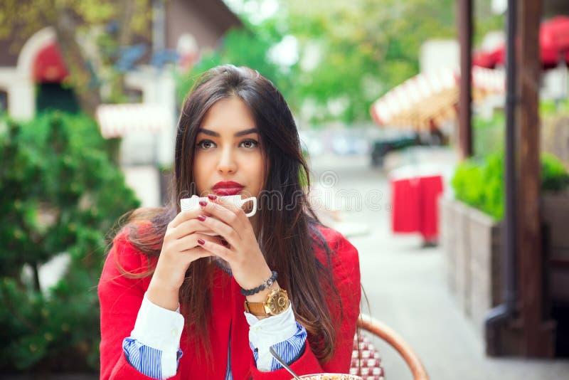 Jovem mulher que pensa guardando o café em um terraço na moda do café imagem de stock