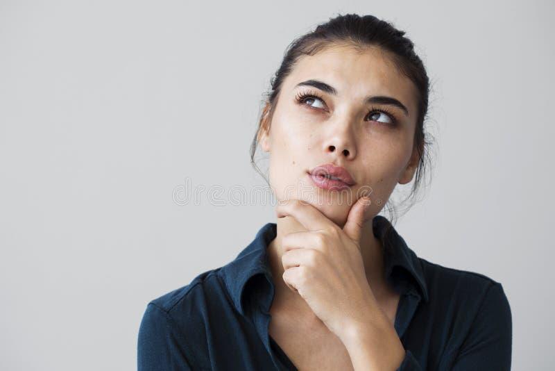 Jovem mulher que pensa no fundo cinzento imagens de stock royalty free