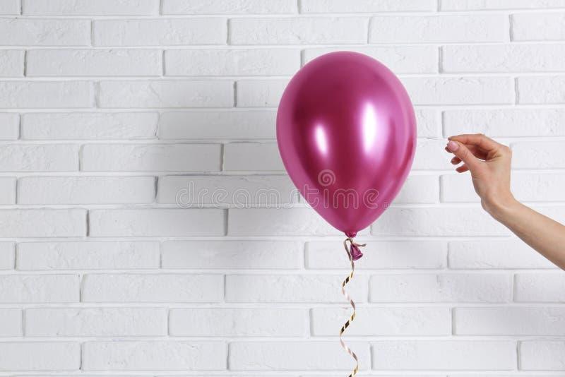 Jovem mulher que perfura o balão brilhante perto da parede, espaço para o texto fotos de stock royalty free
