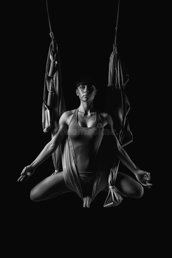Jovem mulher que pratica a rede aérea da ioga imagens de stock