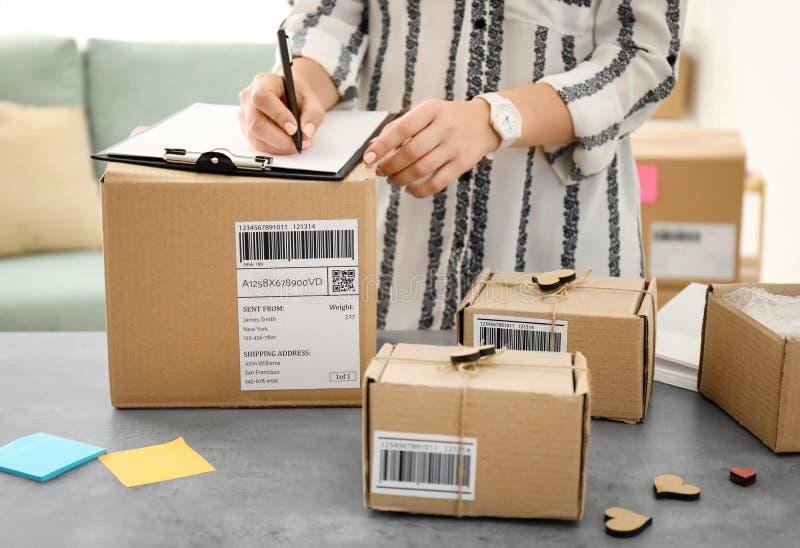Jovem mulher que prepara pacotes para a expedição fotos de stock royalty free
